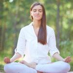 dziewczyna medytuje w kwiecie lotosu w lesie