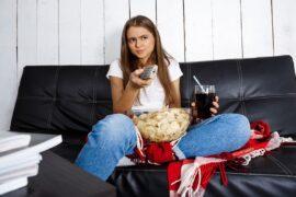 Dziewczyna z chipsami i napojem ogląda TV