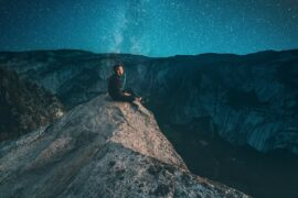 mężczyzna patrzy na gwiazdy w górach